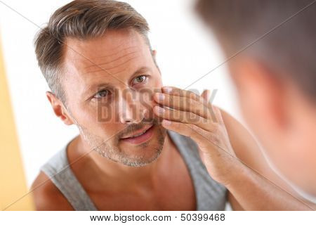 Man in bathroom applying cosmetics on his face