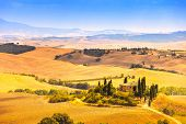 pic of farm landscape  - Tuscany farmland and cypress trees country landscape green fields. San Quirico Orcia Italy Europe.