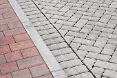 stock photo of paved road  - Brick paving types with pink sidewalk curb and drive made from plain interlocking concrete bricks - JPG