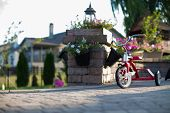 stock photo of tricycle  - Childs red tricycle parked on a paved patio overlooking a garden in a shaft of sunlight - JPG