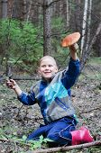 stock photo of face-fungus  - The joyful boy in wood holds in a hand the big aspen mushroom which it has found - JPG