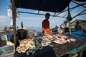 PADANG - AUGUST 25: A fishmonger waits for customers in a stall at an outdoor village market in Pada