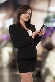 foto of coy  - Beautiful business woman flashes a coy smile while using her phone - JPG