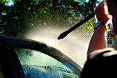 stock photo of pressure-wash  - man washing car in sunshine with high pressure washer - JPG