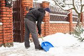 stock photo of snow shovel  - Young man remove snow near the suburban house - JPG