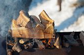 stock photo of inflamed  - inflames smoking logs in the grill outdoors - JPG