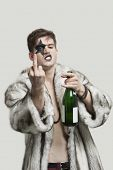 picture of obscene gesture  - Portrait of young man with a rude gesture while holding beer bottle against gray background - JPG