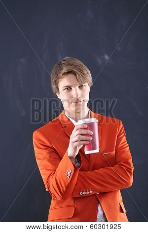 Boy in the orange jacket with a cup of coffee