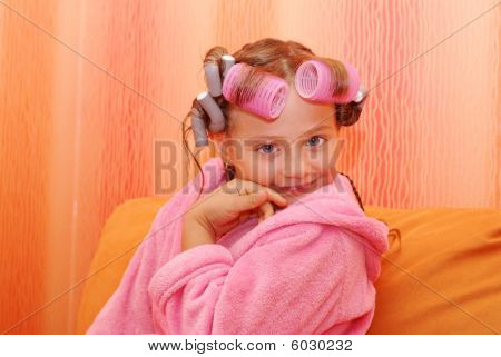 A Child With An Unusual Hairdo Sitting On An Orange Sofa.