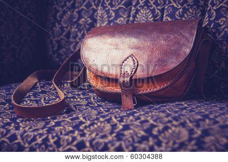 Leather Handbag On Vintage Sofa