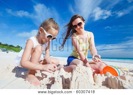 Young mother and her little daughter at tropical beach making sandcastle