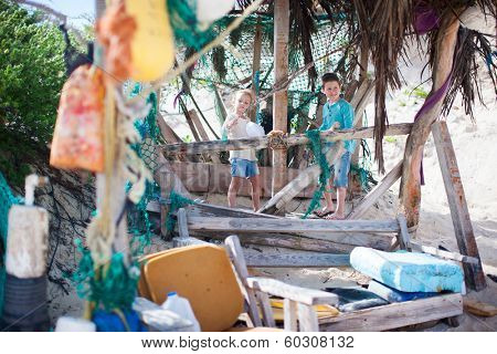Little kids exploring rustic beach hut