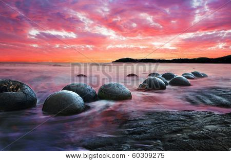 Moeraki Boulders on the Koekohe beach, Eastern coast of New Zealand. Sunset and long exposure