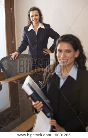 Two hispanic businesswomen standing in boardroom