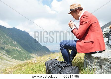 picture of a young fashion man lighting up a cigarette outdoor, in the mountains while sitting on a rock, with a breathtaking landscape behind him
