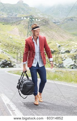 picture of a young fashion man walking on the middle of the road in the mountains while holding a bag in his hand and looking down, away from the camera