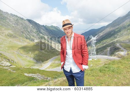 portrait of a young fashion man posing outdoor, with his hands in his pockets while looking into the camera, over a breathtaking landscape of the Transfagarasan road