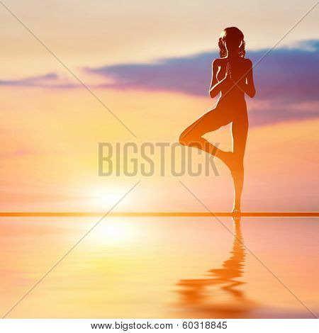 A silhouette of a woman standing in tree yoga position, meditating against sunset sky. Zen, meditation