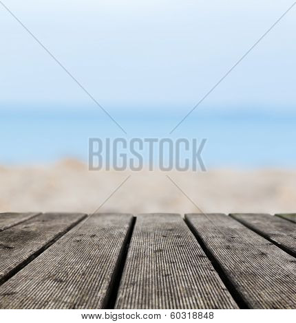 Grunge rustic real wood boards on the beach shore, ocean background. Place for an object.