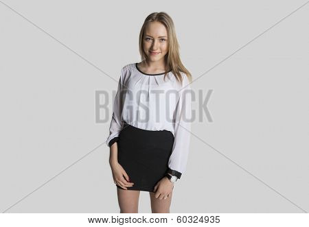 Portrait of smiling girl wearing mini dress over gray background