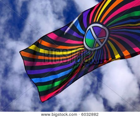 Multi - colored flag against a blue cloudy sky background