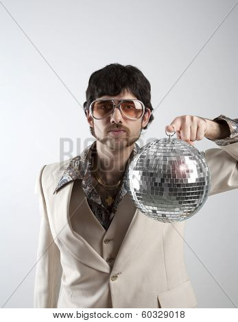 Portrait of a retro man in a 1970s leisure suit and sunglasses holding a disco ball
