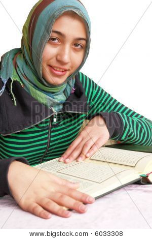 Muslim girl reads Koran - isolated on white background