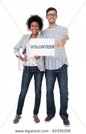 Full length portrait of a happy couple holding a volunteer note over white background