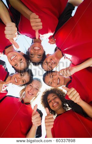 Directly below shot of female soccer team gesturing thumbs up while forming huddle against clear sky
