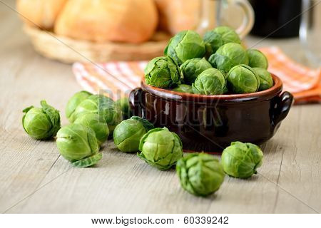 Bruxelle sprouts in a bowl on a rustic wooden table . behind there is a bottle of olive oil, a towel and a basket of bread
