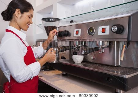 Pretty barista steaming jug of milk at coffee machine in a cafe