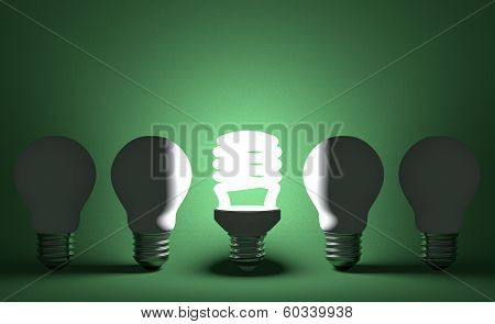 Glowing Spiral Light Bulb In Row Of Dead Tungsten Ones On Green