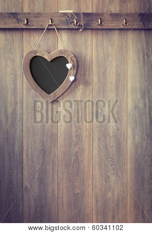 Heart shape menu board hanging on wooden panel wall - vintage tone effect added to wood