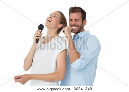 Cheerful couple singing into microphones over white background
