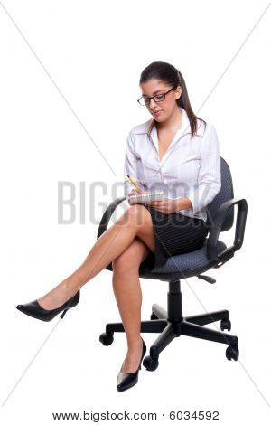 Secretary Sat On An Office Chair Taking Notes.