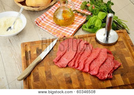 cut slices of raw meat on cutting board with knife and tamp steaks