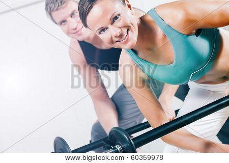 attractive couple in sport gym doing power gymnastics training with barbells