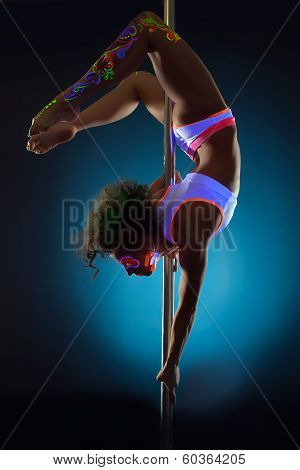Image of slim girl dancing on pole under UV light