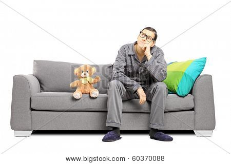 Young man in pajamas deep in thoughts seated on a sofa with teddy bear next to him isolated on white background