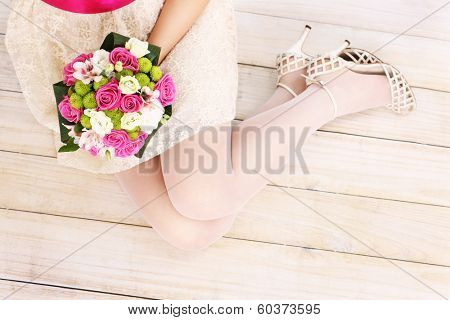 A picture of bride's legs and flowers on wooden floor