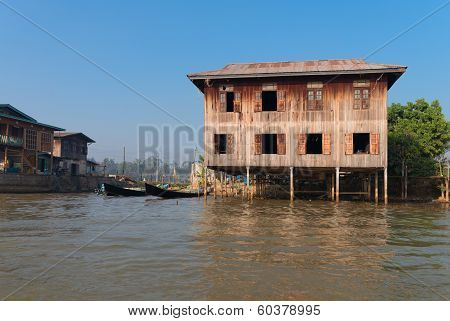 Traditional Stilts House And Boat In Water Under Blue Sky
