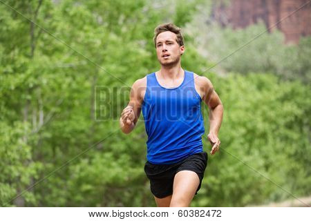 Sport running fitness man training towards goals. Fit male runner sprinting and jogging training outside in forest for marathon run. Muscular handsome Caucasian model in his 20s.