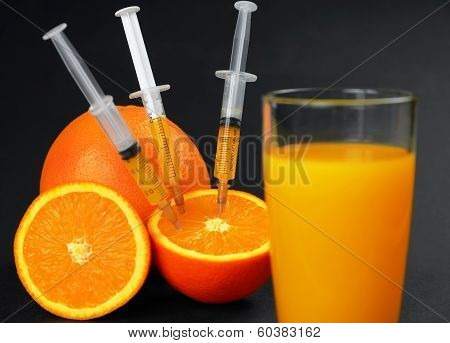 Syringes Injected Into Orange And Juice