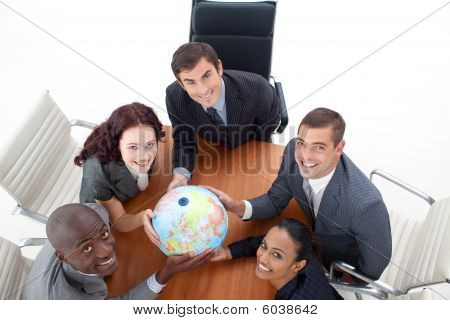 High View Of Happy Business People Holding A Globe. Global Business