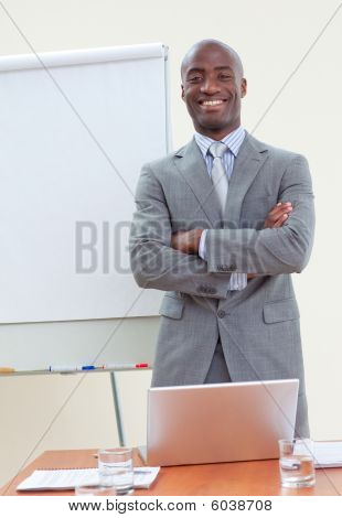 Confident Ethnic Businessman In Office With Folded Arms