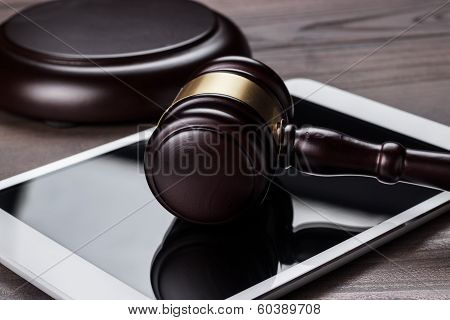 judge gavel and tablet computer on brown wooden backgroundjudge gavel and tablet computer on the tab