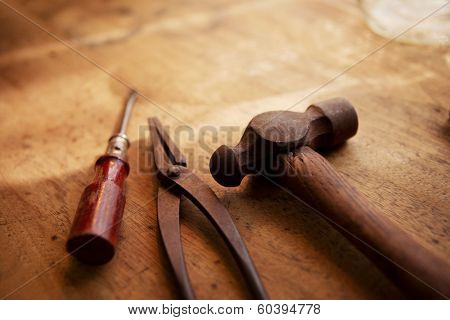 Craftsman's tools. Old and well used hammer, pliers and screw driver on a old wooden desk. With warm lighting.