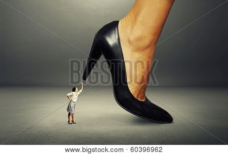small angry woman showing fist and screaming at boss