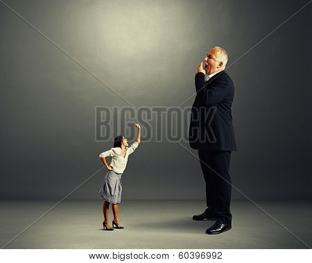 angry woman screaming at big yawning boss over dark background