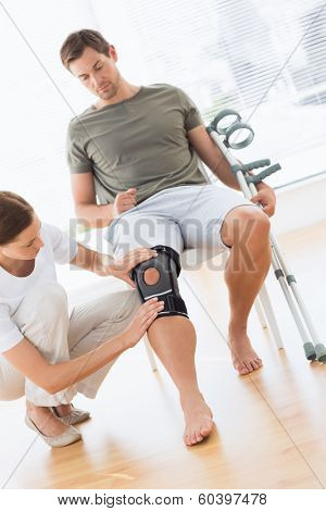 Female physiotherapist checking man with crutches in hospital